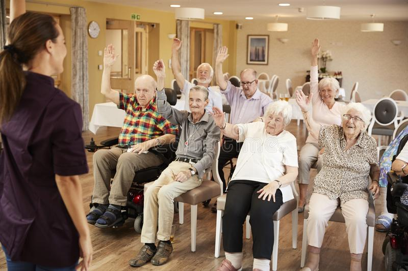 Carer Leading Group Of Seniors In Fitness Class In Retirement Home stock photos