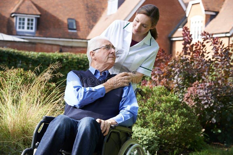 Carer Pushing Senior Man In Wheelchair stock image