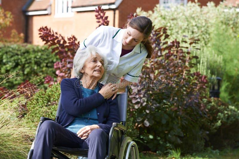 Carer Pushing Senior Woman In Wheelchair stock image