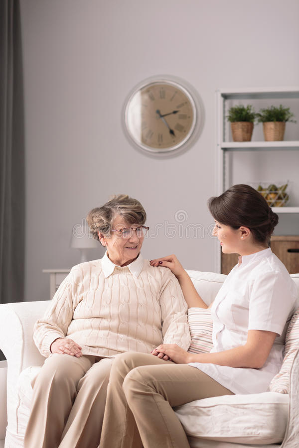 Carer supporting elderly woman royalty free stock image