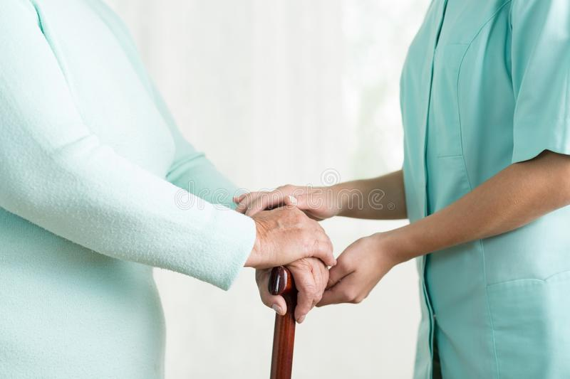 Carergiver holding hand of female. Close up of caregiver holding hand of old female stock photography