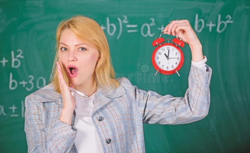 She cares about discipline. What time is it. Woman teacher hold alarm clock. Girl formal wear school lecturer. Time to stock images