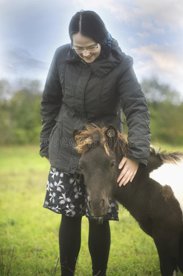 Caressing a litlle pony horse youngster stock photography
