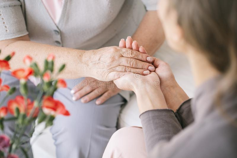 Caretaker giving her hand. Young caretaker giving her helpful hand to an older woman stock image