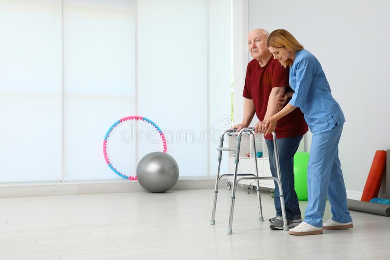 Caretaker helping elderly  with walking frame indoors stock photo