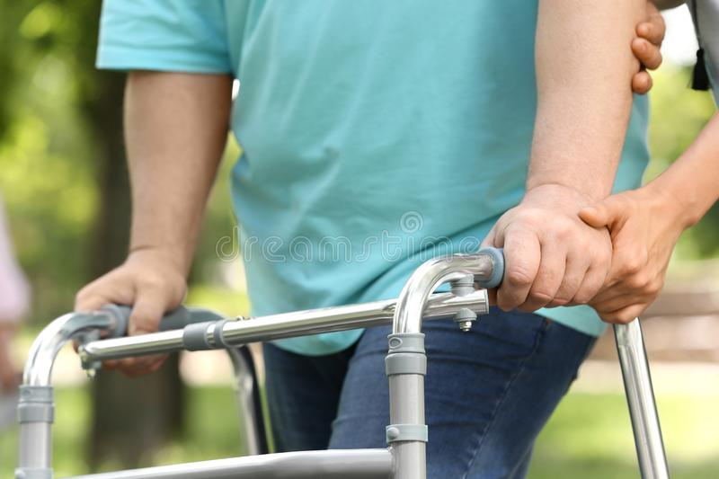 Caretaker helping elderly man with  frame outdoors, stock photography