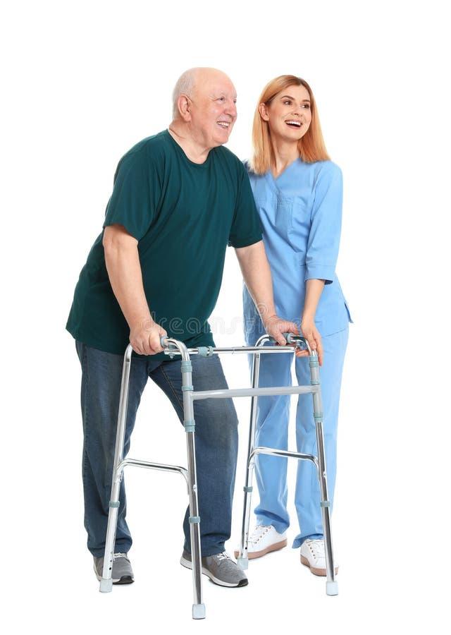 Caretaker helping elderly man with walking frame on white royalty free stock photo