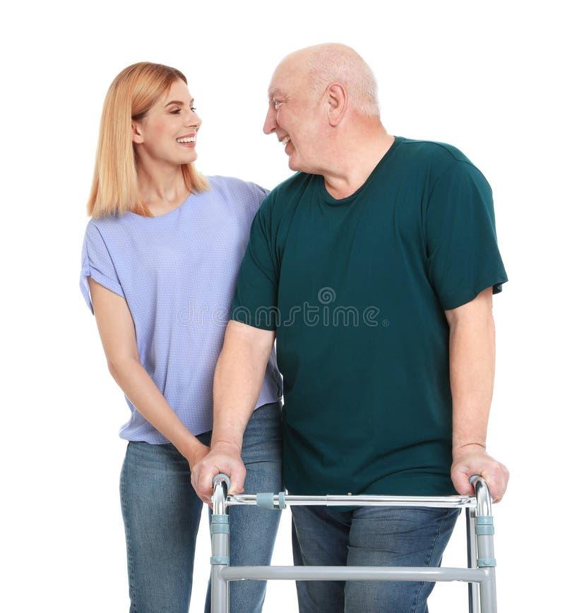 Caretaker helping  man with walking frame on white background stock photo