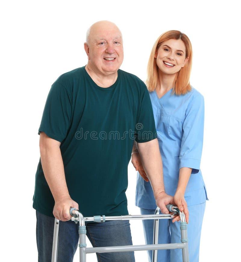 Caretaker helping elderly man with walking frame royalty free stock image