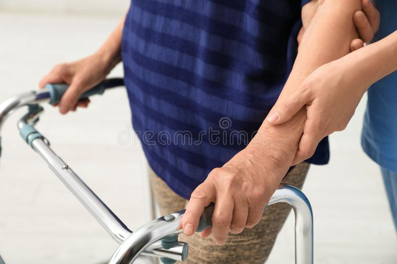 Caretaker helping elderly woman with walking frame on background, closeup stock images
