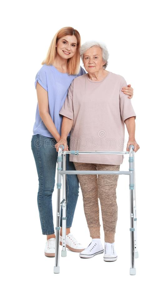 Caretaker helping elderly woman with walking frame on white royalty free stock image