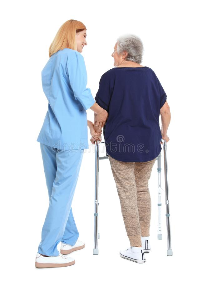 Caretaker helping elderly woman with walking frame on white stock photo