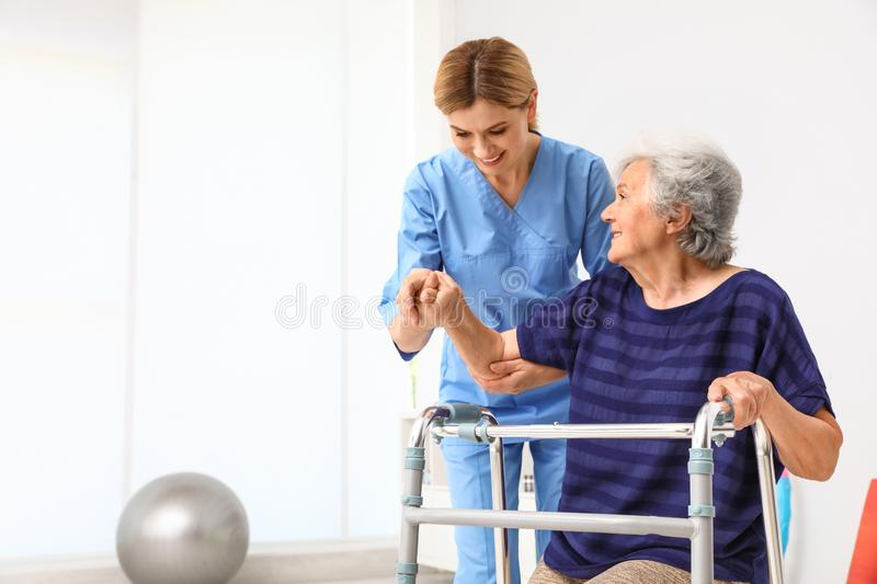 Caretaker helping elderly woman with walking frame stock photography