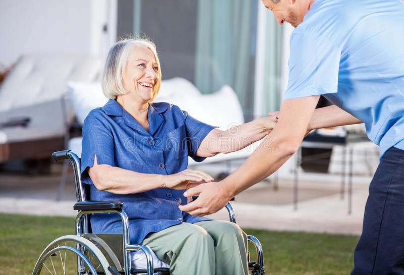 Caretaker Helping Senior Woman To Get Up From stock photography