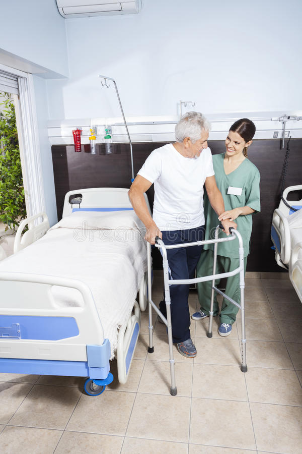 Caretaker Looking At Senior Patient Using Walker stock photo