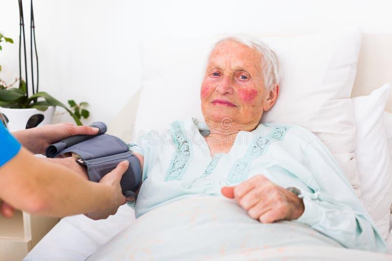Caretaker measuring blood pressure. Happy senior woman having her blood pressure measured in bed in a nursing home by her caregiver stock photos