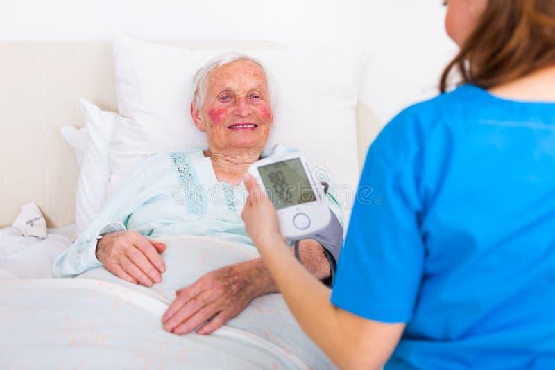 Caretaker measuring blood pressure. Happy senior women having her blood pressure measured in bed in a nursing home by her caregiver royalty free stock photo