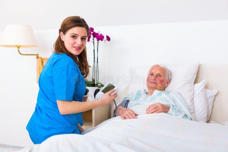Caretaker measuring blood pressure. Happy senior women having her blood pressure measured in bed in a nursing home by her caregiver royalty free stock image