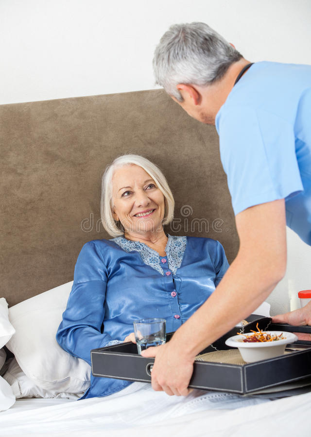 Caretaker Serving Breakfast To Happy Senior Woman stock image