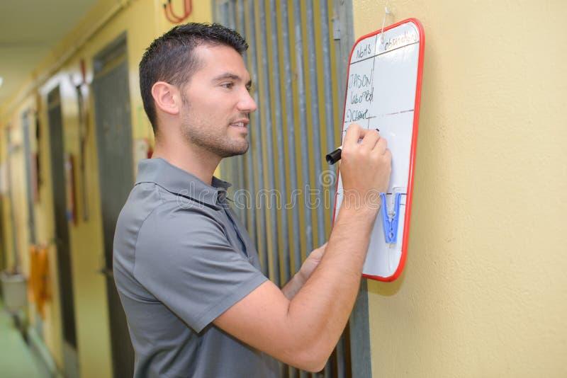 Caretaker writing on whiteboard stock image