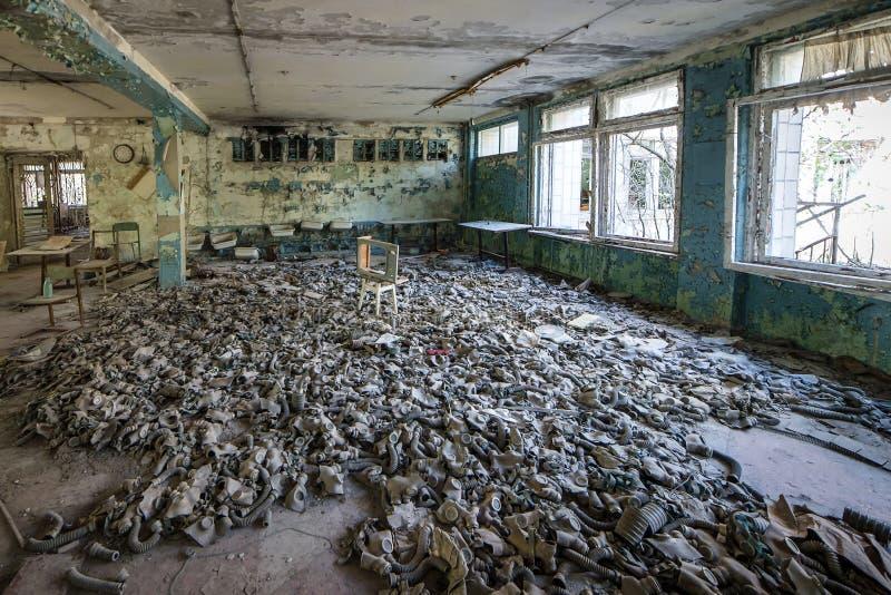 Caretas antig?s en el piso en la escuela secundaria en Pripyat, zona de exclusi?n de Chern?bil Cat?strofe nuclear fotografía de archivo
