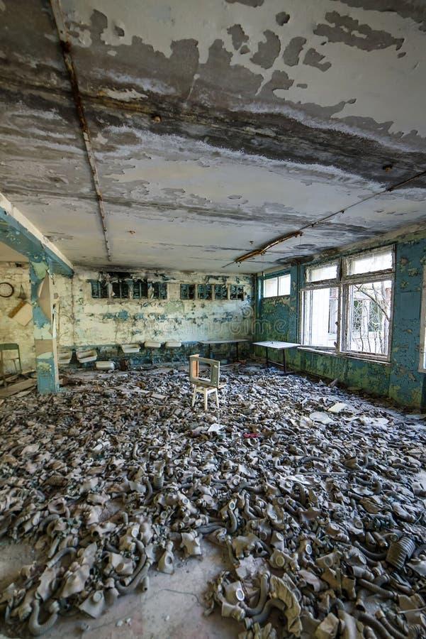 Caretas antig?s en el piso en la escuela secundaria en Pripyat, zona de exclusi?n de Chern?bil Cat?strofe nuclear foto de archivo libre de regalías