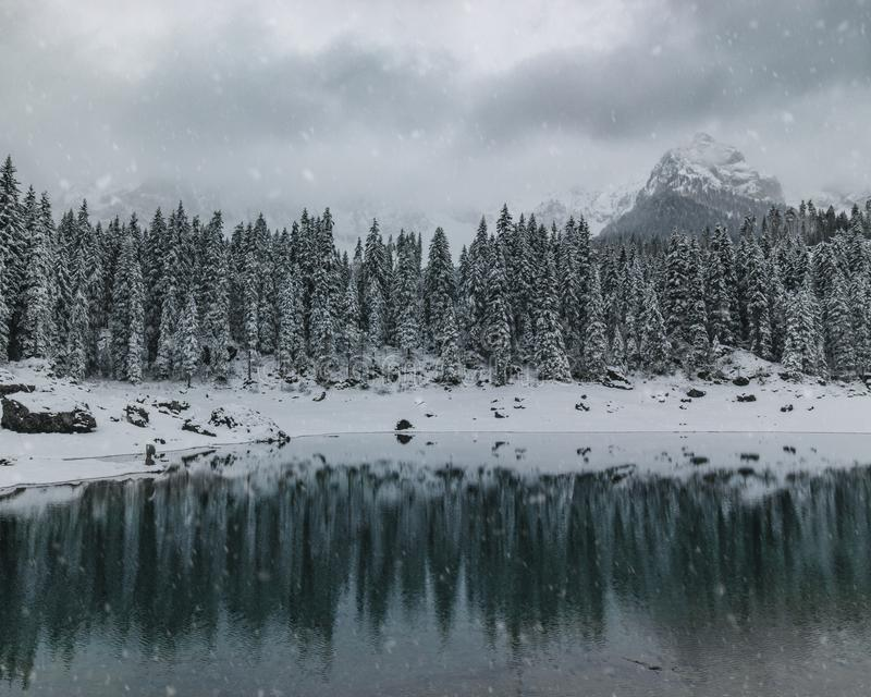 Carezza del lago con le montagne durante il giorno nevoso immagine stock libera da diritti