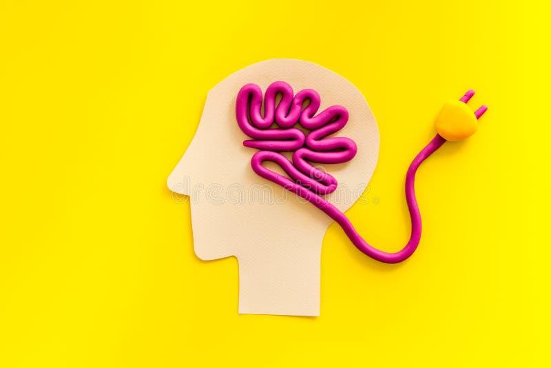 Carga cerebral e repouso mental O cabo e o plugue levam a serpentes de linha plasmática sobre fundo amarelo foto de stock royalty free