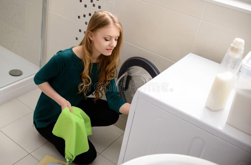 A carga da mulher veste-se na máquina de lavar imagem de stock