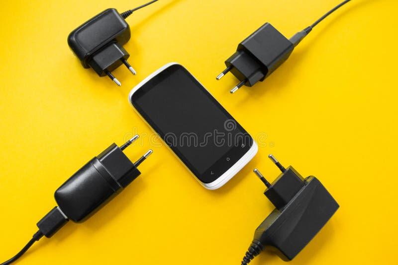 Carga inalámbrica para el smartphone en un fondo amarillo, concepto fotos de archivo libres de regalías
