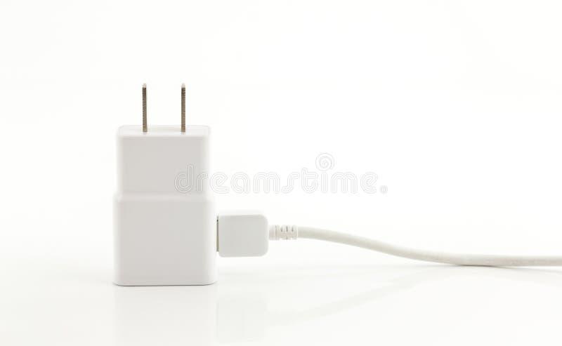 Cargador blanco del adaptador con el cable del usb en el fondo blanco imagenes de archivo