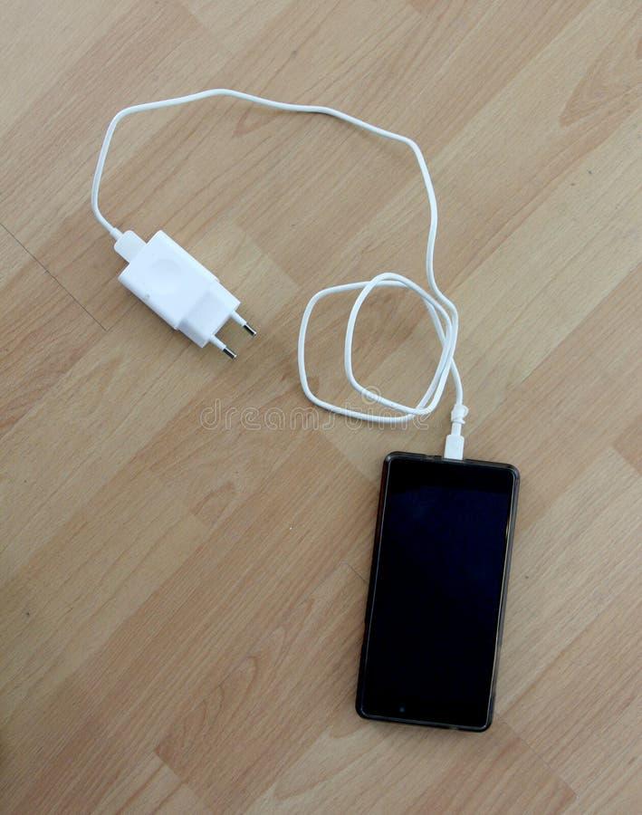 cargador blanco del smartphone en el fondo de madera fotos de archivo libres de regalías