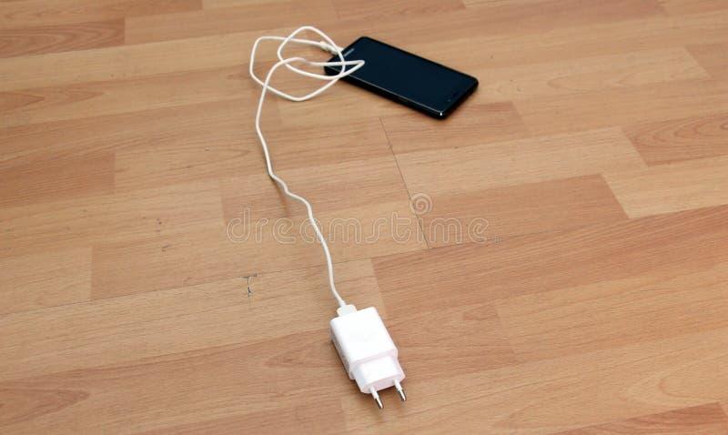cargador blanco del smartphone en el fondo de madera imagen de archivo libre de regalías