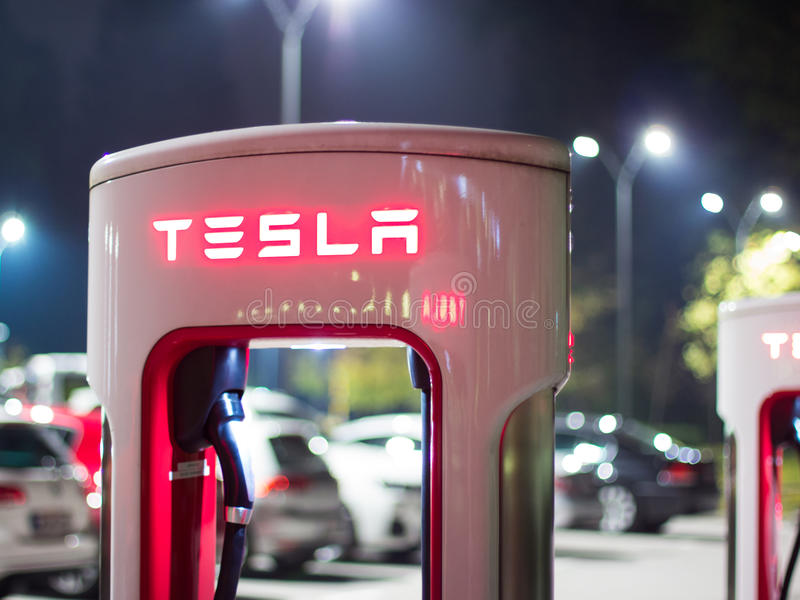Cargador del coche de Tesla en la noche fotografía de archivo libre de regalías