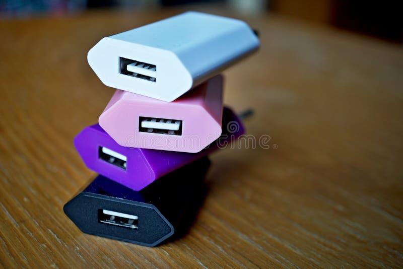 Cargadores coloridos del poder con los conectores del USB (bus de serie universal) para un punto de poder fotos de archivo