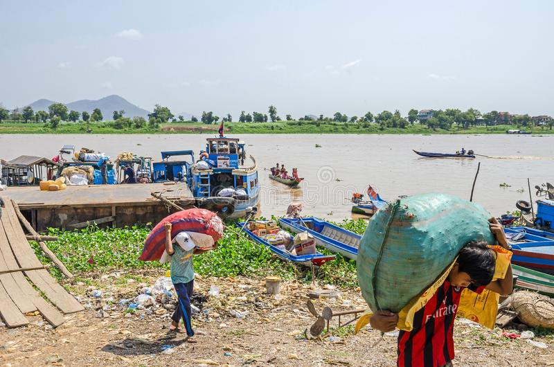 Cargadores que llevan los sacos pesados que descargan la nave de la carga en el banco del río Mekong en Camboya fotos de archivo libres de regalías