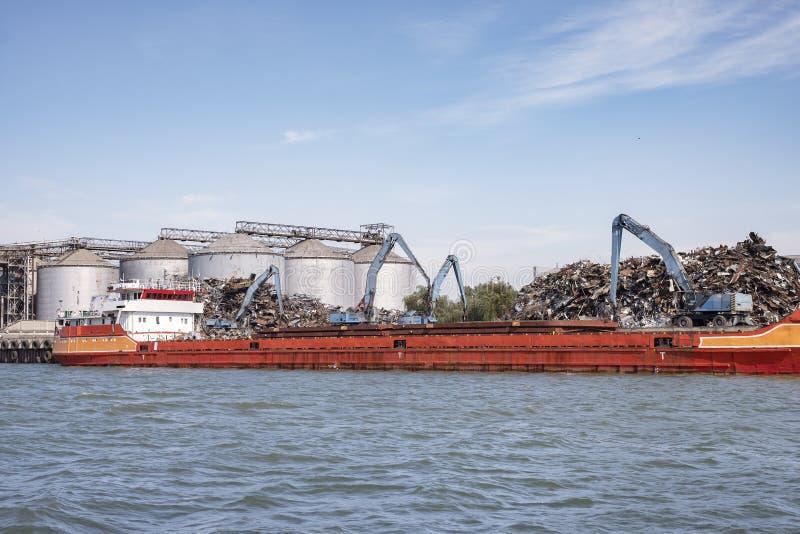 Cargamento de la chatarra en una nave en el puerto Se está cargando la gabarra, foto de archivo