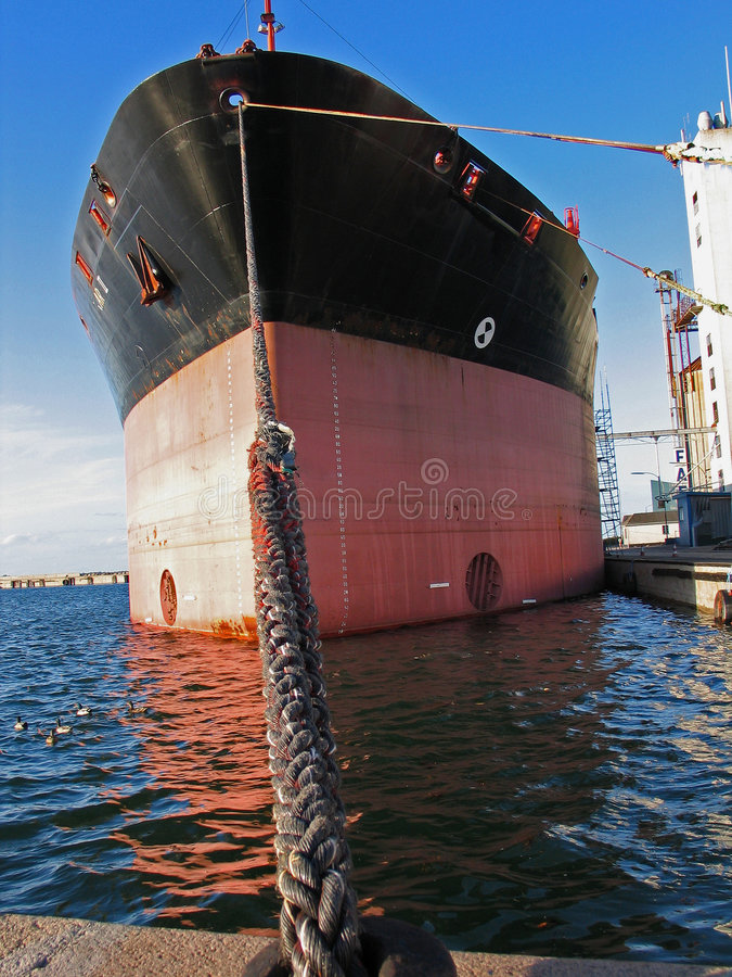 Cargo boat moored in a port. Commercial Cargo boat moored to a dock in a port royalty free stock images