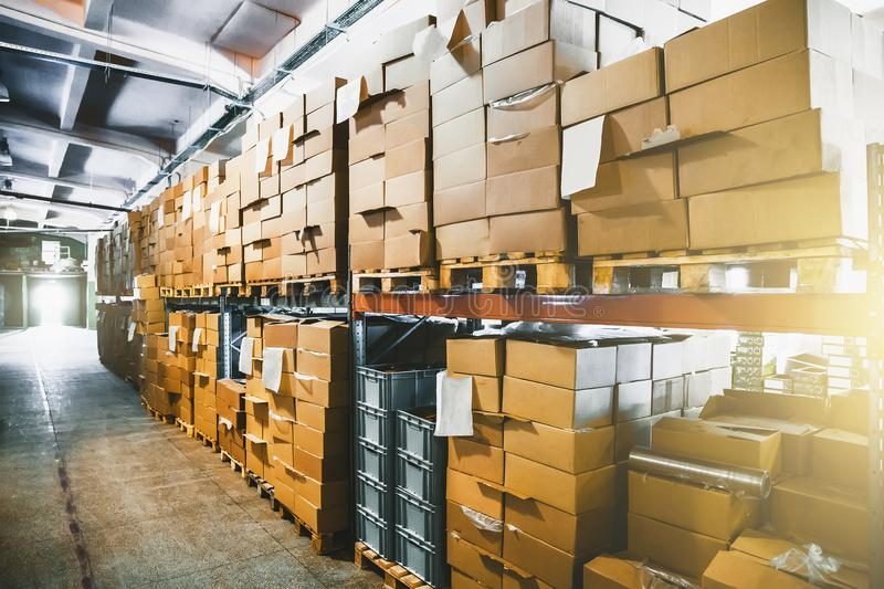Cargo cardboard boxes for shipping and delivery in logistic storage warehouse hangar, interior of storehouse inside. Toned royalty free stock images