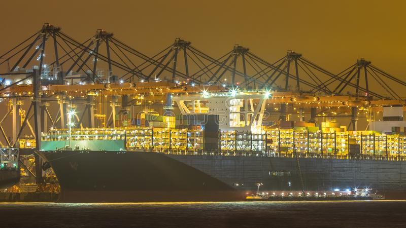 Cargo carrier ship being loaded and refueled at night royalty free stock photo