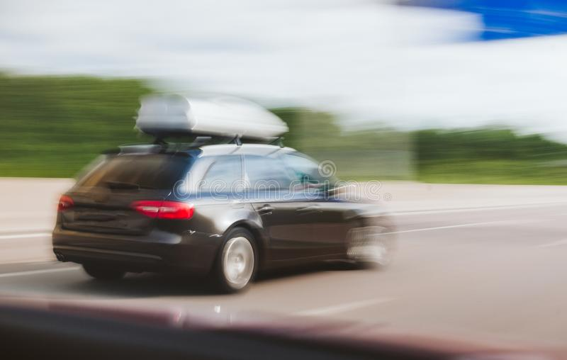 Cargo carrier on top of wagon car driving fast on highway royalty free stock image