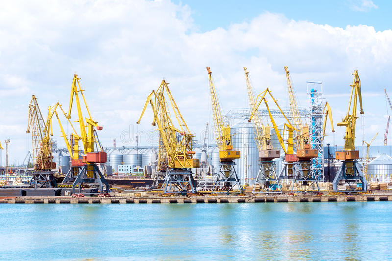 Cargo container terminal of sea freight industrial port. Port cargo cranes over blue sky background. Large elevator in the s stock photos