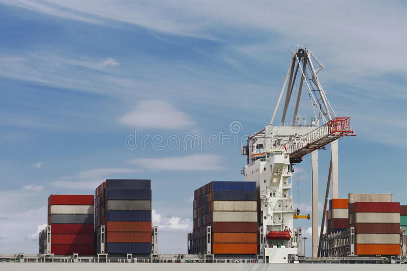 Cargo containers ready for shipping. Transport Cargo Ship loaded with containers by a crane in a harbor stock image