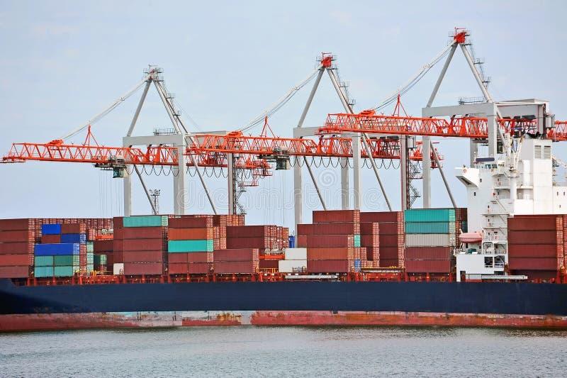 Cargo crane and ship. Container stack and ship under crane bridge stock image
