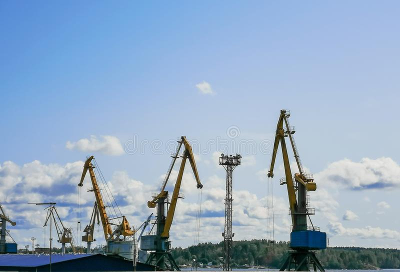 Cargo cranes in a commercial sea (river) port on a sunny day. Logistics, equipment, trade, sky, blue, nobody, outdoor, objects royalty free stock photos