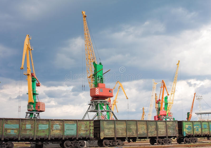 Cargo cranes and wagons in port. Huge seaport cranes in front of railway with wagons stock image