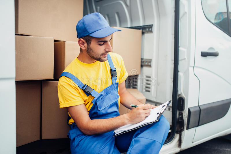 Cargo delivery, courier and truck with boxes. Cargo delivery service, male courier in uniform and truck with cardboard boxes.Empty container royalty free stock photography