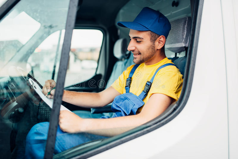 Cargo delivery, driver courier sitting in truck. Cargo delivery service, male driver courier in uniform sitting in cab of truck. Distribution business stock image