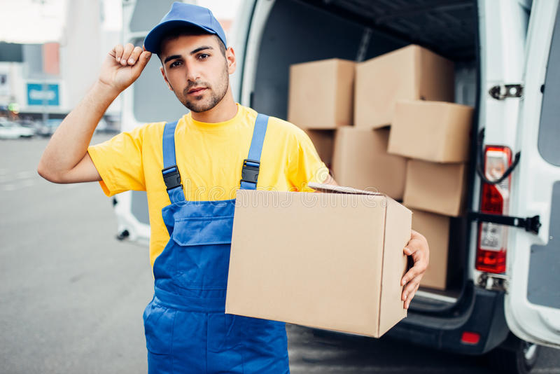 Cargo delivery, male courier with box in hand. Cargo delivery service, male courier in uniform with box in hand and truck with cardboard parcels. Empty container royalty free stock photo