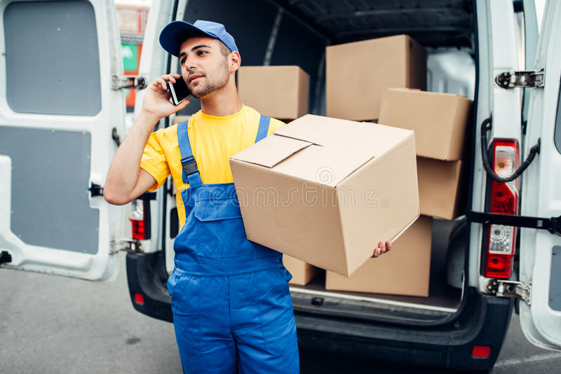 Cargo delivery service, courier with box and phone stock image